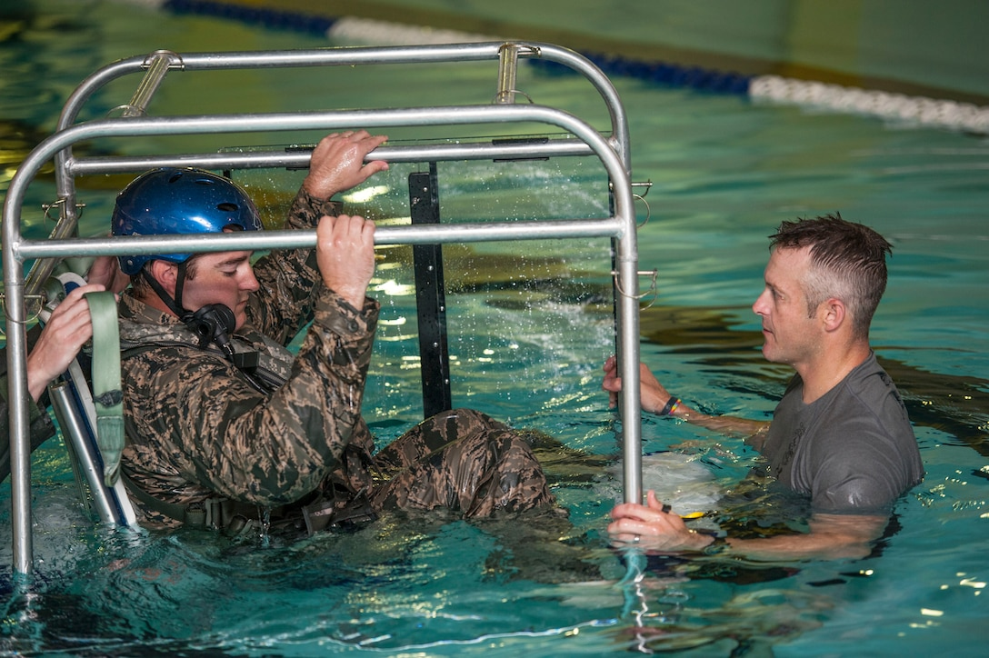 (From left) Capt. David Shadoin, 54th Helicopter Squadron pilot, is briefed by Tech. Sgt. Clifton Cleveland, 5th Operations Support Squadron survival, evasion, resistance and escape specialist, during underwater survival training at Minot Air Force Base, N.D., June 22, 2017. The shallow water egress trainer allows Airmen to practice escape procedures during a simulated helicopter crash. (U.S. Air Force photo by Airman 1st Class Jonathan McElderry)