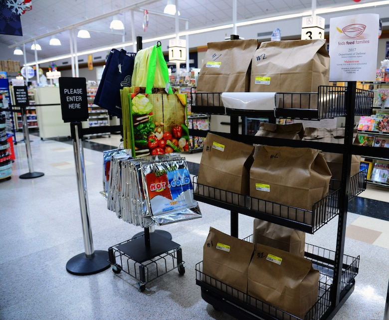 A stand of premade Feds Feed Families donation bags are displayed June 29, 2017, at Malmstrom Air Force Base, Mont. The Malmstrom Commissary curated bags for convenient donation; one for food items and one for non-food items, such as toiletries. (U.S. Air Force photo/Senior Airman Magen M. Reeves)