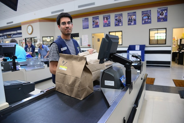 A commissary teller rings up a customer's purchase of two Feds Feed Families donation bags June 29, 2017, at Malmstrom Air Force Base, Mont. The Malmstrom Commissary acts as a direct link between the donating customers and the local charity for distribution. (U.S. Air Force photo/Senior Airman Magen M. Reeves)