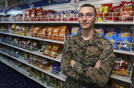Lance Cpl. Kaenon Ralls of Easton, Kan., works as a supply administrator for Marine Medium Tiltrotor Squadron 161 (Reinforced), 15th Marine Expeditionary Unit (MEU), and is currently temporarily assigned to the ship store , where comfort items, hygiene gear and some uniform items are available for Marines and Sailors aboard amphibious assault ship USS AMERICA (LHA 6) during underway periods. (U.S. Marine Corps photo by Cpl. Nathaniel S. McAllister)
