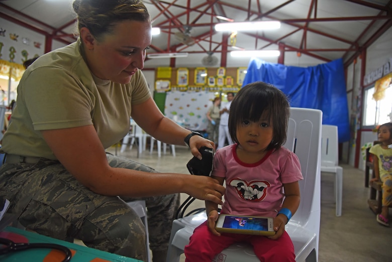 U.S. Air Force Senior Airman Danielle Delporto, medical technician with the 152nd Medical Group, Nevada Air National Guard, measures the vitals of a girl from Bogo City during Pacific Angel 2017 in Northern Cebu Province, Philippines, June 26, 2017. PACANGEL participants from six different nations work together with local nongovernmental organizations to administer medical care, including general health, optometry, dental, physical therapy and pediatrics, to the people of Northern Cebu Province. (U.S. Air Force photo by Tech. Sgt. Jeff Andrejcik)