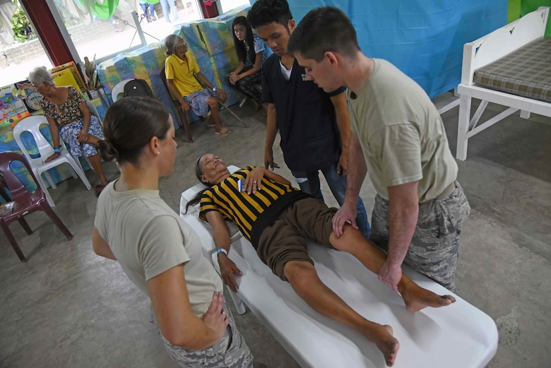 The 2017 Pacific Angel physical therapy team works on a woman from Bogo City during PACANGEL in Northern Cebu Province, Philippines, June 26, 2017. PACANGEL participants from six different nations work together with local nongovernmental organizations to administer medical care, including general health, optometry, dental, physical therapy and pediatrics, to the people of Northern Cebu Province. (U.S. Air Force photo by Tech. Sgt. Jeff Andrejcik)