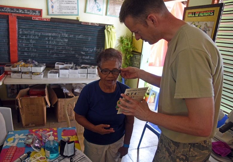 U.S. Air Force Maj. Jay Butler, optometrist with the 374th Medical Group, Yokota Air Base, Japan, tests the eye sight of a woman from Bogo City during Pacific Angel 2017 in Northern Cebu Province, Philippines, June 26, 2017. PACANGEL participants from six different nations work together with local nongovernmental organizations to administer medical care, including general health, optometry, dental, physical therapy and pediatrics, to the people of Northern Cebu Province. (U.S. Air Force photo by Tech. Sgt. Jeff Andrejcik)