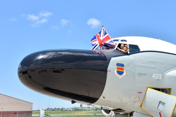 British Royal Air Force Squadron Leader Ade Pickup, an exchange officer with the 338th Combat Training Squadron, flies the United Kingdom flag and poses with Hugh Trenchard, a special teddy bear, following a training flight on an RC-135 here June 29. Hugh is an honorary member of the RAF and has been flying on aircraft all across the U.S. this year to commemorate the 100th anniversary of the Royal Air Force in 1918 and also the U.S. Air Force 70th anniversary this year. (U.S. Air Force photo by Charles Haymond)