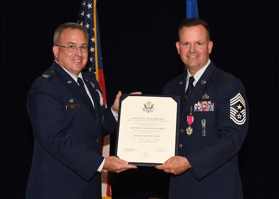 Retired Col. J. Christopher Moss, former 30th Space Wing commander, presents a certificate of retirement to Chief Master Sgt. Robert Bedell, 30th SW command chief, June 29, 2017, Vandenberg Air Force Base, Calif. Bedell, who served for 29 years, sat down before his retirement for some final words to the base to share years of experience and expertise with fellow Airmen one final time as a command chief. (U.S. Air Force photo by Senior Airman Kyla Gifford/Released)