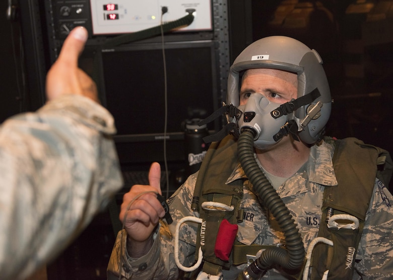 Master Sgt. Eric Icenhower, 141st Air National Guard Survival Evasion Resistance and Evasion liaison, gives the thumbs-up before starting a simulation on the Reduced Oxygen Breathing Device June 26, 2017, at Fairchild Air Force Base, Washington. The ROBD can simulate high altitude atmospheric pressures to induce a controlled state of hypoxia in trainees. (U.S. Air Force Photo / Airman 1st Class Ryan Lackey)