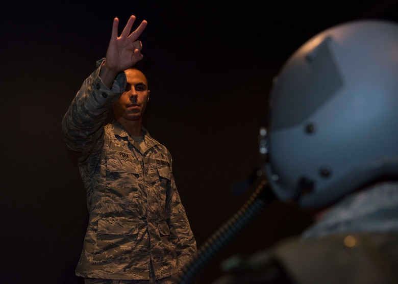 Tech. Sgt. Oscar Pena, 92nd Aerospace Medicine technician, gives a three minute warning to Master Sgt. Eric Icenhower, 141st Air National Guard SERE liaison, during a Reduced Oxygen Breathing Device simulation June 26, 2017, at Fairchild Air Force Base, Washington. SERE specialists use the ROBD to simulate high altitude hypoxia effects they may experience on a parachute jump mission. (U.S. Air Force Photo / Airman 1st Class Ryan Lackey)