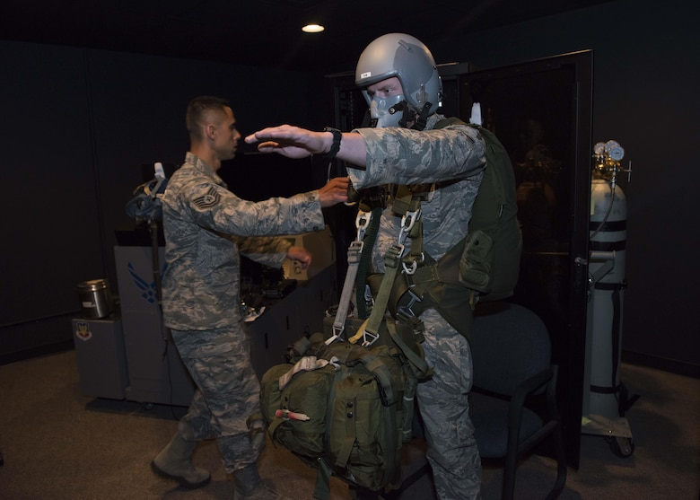 Tech. Sgt. Oscar Pena, 92nd Aerospace Medicine technician, moves to assist Airman 1st Class Jeff Eisberg, 22nd Training Group Survival Evasion Resistance and Evasion specialist, during a Reduced Oxygen Breathing Device simulation June 26, 2017, at Fairchild Air Force Base, Washington. Pilots, air crew and parachutists are trained to raise their left arm to signal they need help when experiencing the effects of hypoxia. (U.S. Air Force Photo / Airman 1st Class Ryan Lackey)