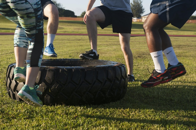Warrior Training Fitness workout attendees use the tire exercise station June 28, 2017, at the Risner Fitness and Sports Complex, Kadena Air Base, Japan. The workout consisted of multiple exercise stations that rotate between varieties of training techniques. (U.S. Air Force photo/Airman 1st Class Greg Erwin)