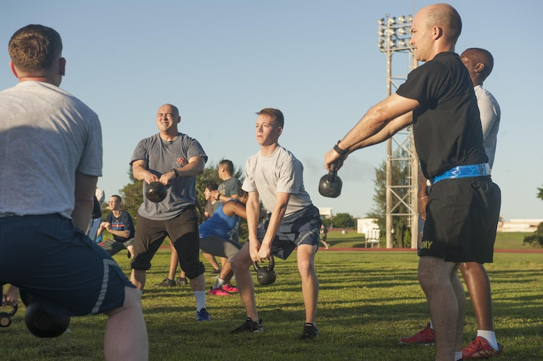 Military members participate in a kettle bell exercise station at a Warrior Training Fitness workout June 28, 2017, at the Risner Fitness and Sports Complex, Kadena Air Base, Japan. Each workout station varies and attendees are at each location for roughly five to ten minutes per station. (U.S. Air Force photo/Airman 1st Class Greg Erwin)