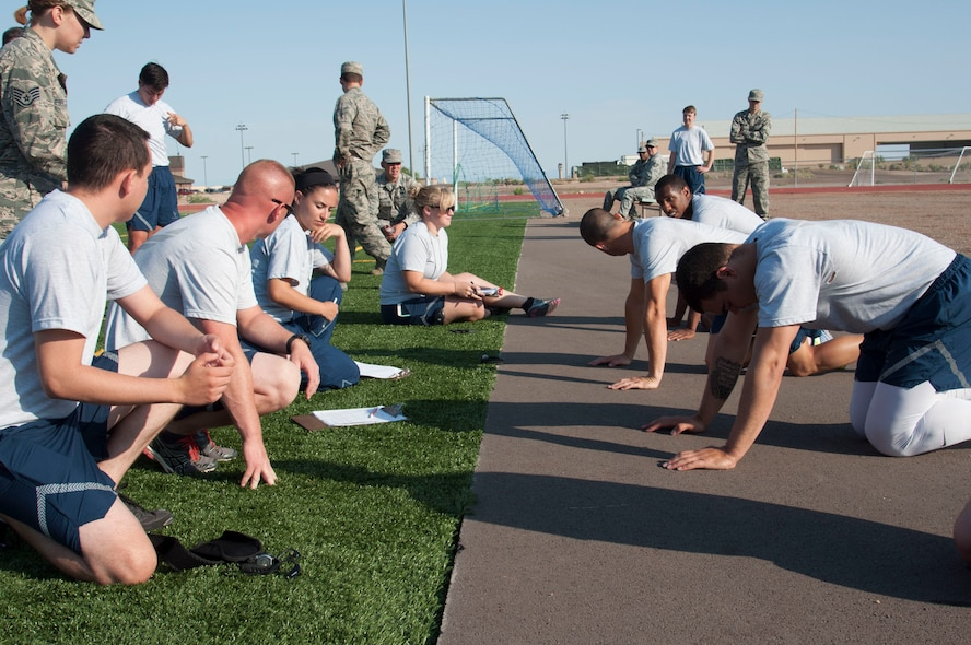 Airmen from the 49th Maintenance Group prepare for the push-up muscular component of the 49th MXG's 101 Days of Training 100 percent PT competition at Holloman Air Force Base, June 27, 2017. On March 6, 2017, the 49th MXG began invigorating the training culture by strengthen the maintainers' competence and focus on upgrade and proficiency training through events such as noncommissioned officer speed mentoring, 100 percent PT competition, 'How to be a Millionaire' brief, and a Consolidated Tool Kit (CTK)/Aircraft Forms and Documentation competition took place over the 15-week period. (Courtesy photo)