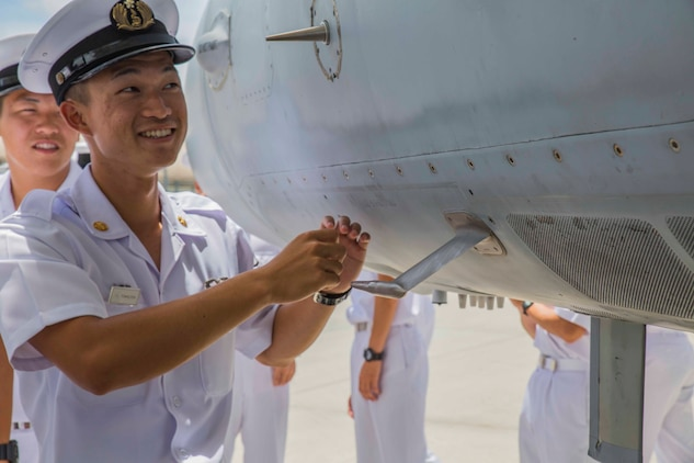 Japan Maritime Self-Defense Force Petty Officer 3rd Class Testsuro, a JMSDF aviation student, looks at an F/A-18C Hornet during a Junior Officer Exchange Program visit at Marine Corps Air Station Iwakuni, Japan, June 21, 2017. Students came from Ozuki Air Base to learn about Marine Air Group (MAG) 12 and the F/A-18. They familiarized themselves with the aircraft during the visit by taking part in a flight simulator and by visiting a static display. (U.S. Marine Corps photo by Lance Cpl. Gabriela Garcia-Herrera)
