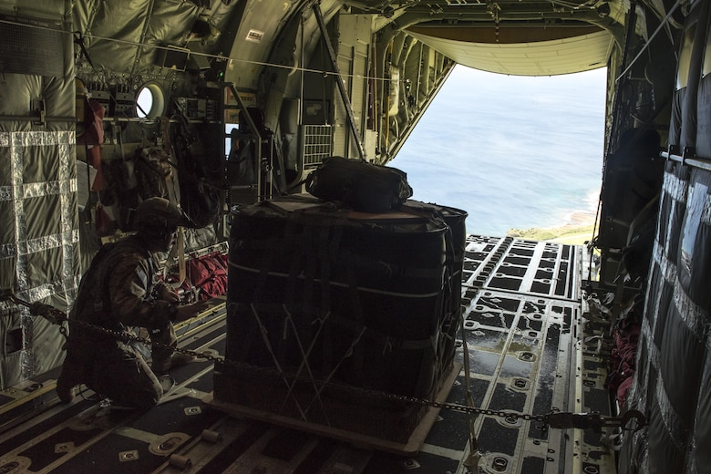 A U.S. Air Force MC-130J Commando II loadmaster from the 17th Special Operations Squadron prepares to airdrop a package onto Le Shima Range, Okinawa, Japan, during a mass launch training mission June 22, 2017. Aircrews must consider a number of variables in order to execute a precise and effective airdrop, to include wind speed, aircraft velocity, altitude, location and timing.  (U.S. Air Force photo by Senior Airman John Linzmeier)