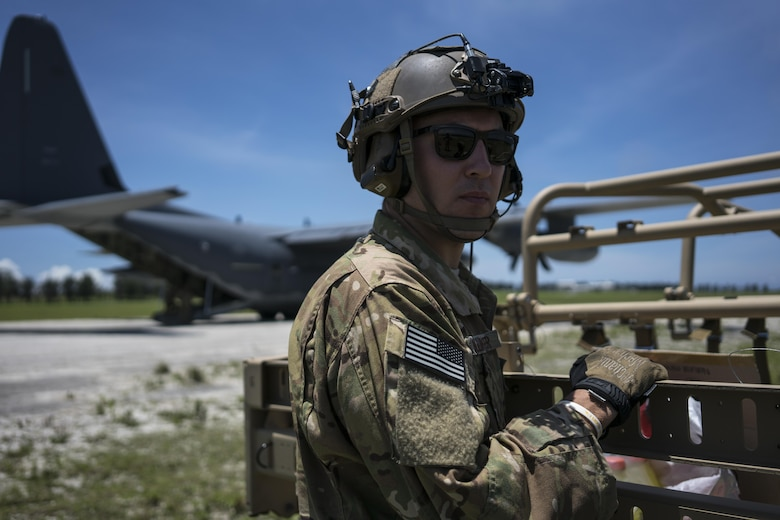 A U.S. Air Force MC-130J Commando II loadmaster assigned to the 17th Special Operations Squadron stands postured to support the rapid infiltration and exfiltration of a tactical vehicle during a mass launch training mission June 22, 2017, at Ie Shima Range, Okinawa, Japan. Airmen from the 17th SOS conduct training operations often to ensure they are always ready perform a variety of high-priority, low-visibility missions throughout the Indo-Asia-Pacific-Region. (U.S. Air Force photo by Capt. Jessica Tait)