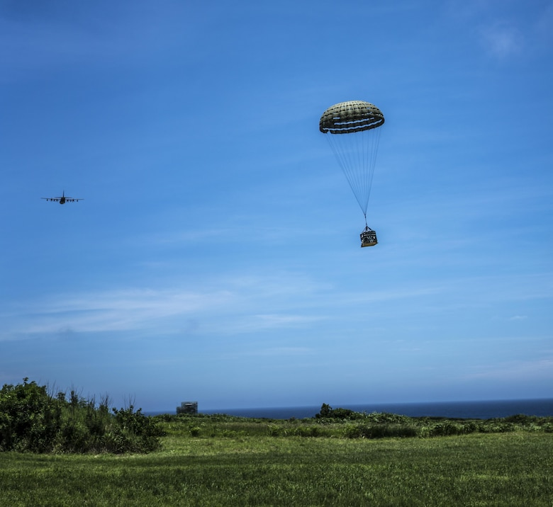 A U.S. Air Force MC-130J Commando II drops a resupply bundle during the airdrop portion of the mass launch training mission June 22, 2017, at Ie Shima Range, Okinawa, Japan. Aircrews must consider a number of variables in order to execute a precise and effective airdrop, to include wind speed, aircraft velocity, altitude, location and timing. (U.S. Air Force photo by Capt. Jessica Tait)