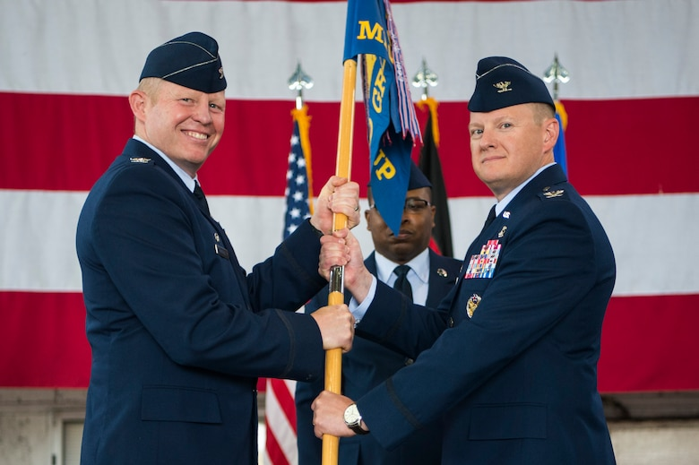 U.S. Air Force Col. Joseph McFall, 52nd Fighter Wing commander, left, gives the ceremonial guidon to U.S. Air Force Col. Edward LaGrou, incoming 52nd Medical Group commander, right, during the 52nd MDG change of command ceremony at Spangdahlem Air Base, Germany, June 29, 2017. (U.S. Air Force photo by Senior Airman Preston Cherry)