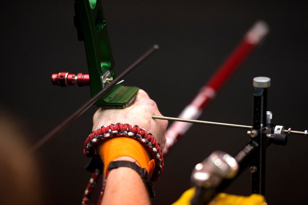 A metal rod serves as a guide to help a visually impaired archer.