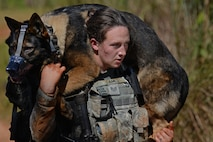Staff Sgt. Victoria Dames, a 35th Security Forces Squadron military working dog handler, carries MWD Elvis during the second annual security forces advanced combat skills assessment at Andersen Air Force Base, Guam, June 6, 2017. The Defenders Challenge provided Airmen with invaluable interaction with other security forces members by exchanging tactics and skills between those in attendance. (U.S. Air Force photo/Airman 1st Class Gerald R. Willis)
