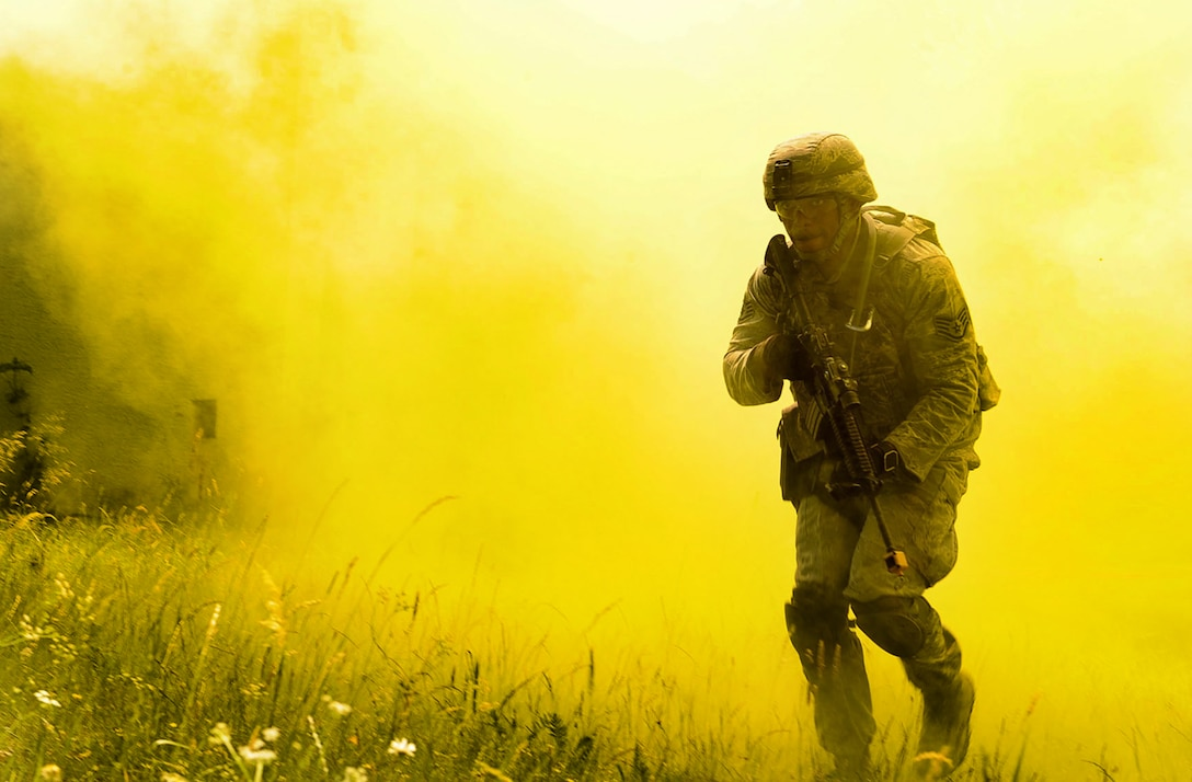 Staff Sgt. Eric Jeffcoat, a 100th Security Forces Squadron base defense operation center controller, emerges from smoke grenade smoke during the 435th SFS's Ground Combat Readiness Training Center Security Operations Course at U.S. Army Garrison Baumholder, Germany, June 15, 2017. Conducting missions as a team and being evaluated by the 435th SFS instructor cadre, students showcased knowledge of urban operations, close quarters combat, live firing iterations, mounted and dismounted patrols, entry control point operations, and counter improved-explosive device operations while at Baumholder. (U.S. Air Force photo/Airman 1st Class Savannah L. Waters)