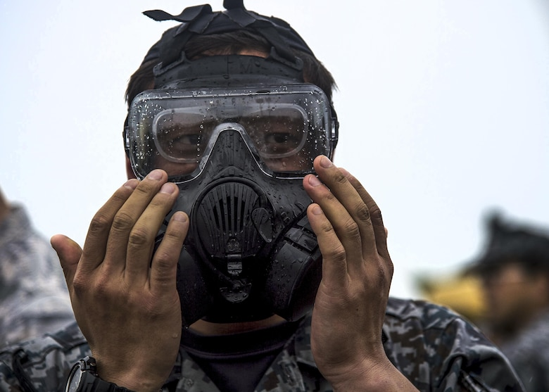 A Japan Air Self-Defense Force civil engineer airman tries on an M50 gas mask during a bilateral exchange event at Misawa Air Base, Japan, June 21, 2017. Building friendships and enhancing mutual understanding were also vital pieces in this Pacific unity event. After long days of training, U.S. and Japanese CE airmen put on civilian clothes and hosted informal dinners to promote international partnerships. (U.S. Air Force photo/Senior Airman Deana Heitzman)