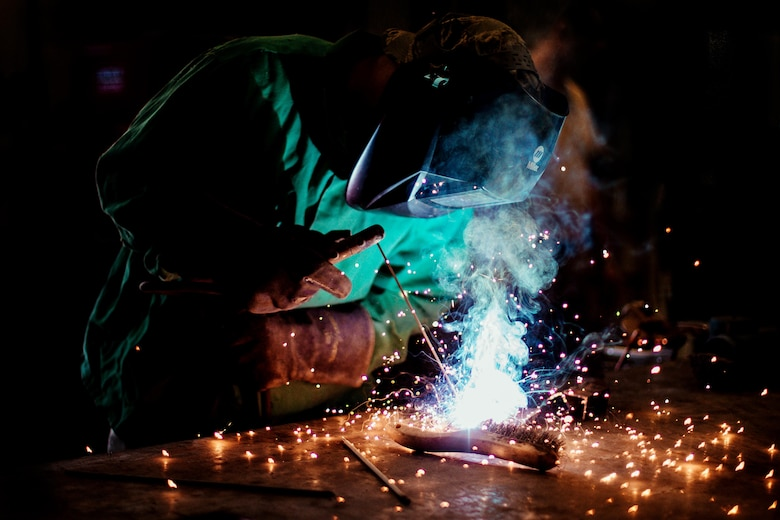 Airman 1st Class Hogan Lambeth, an 11th Civil Engineer Squadron structural apprentice, welds a metal rod at Joint Base Andrews, Md., June 21, 2017. As a metals structural technician, Lambeth is called on to complete welding, sheet metal, duct work, fabrication and repairs to maintain equipment and facilities throughout the base. (U.S. Air Force photo/Senior Airman Delano Scott)