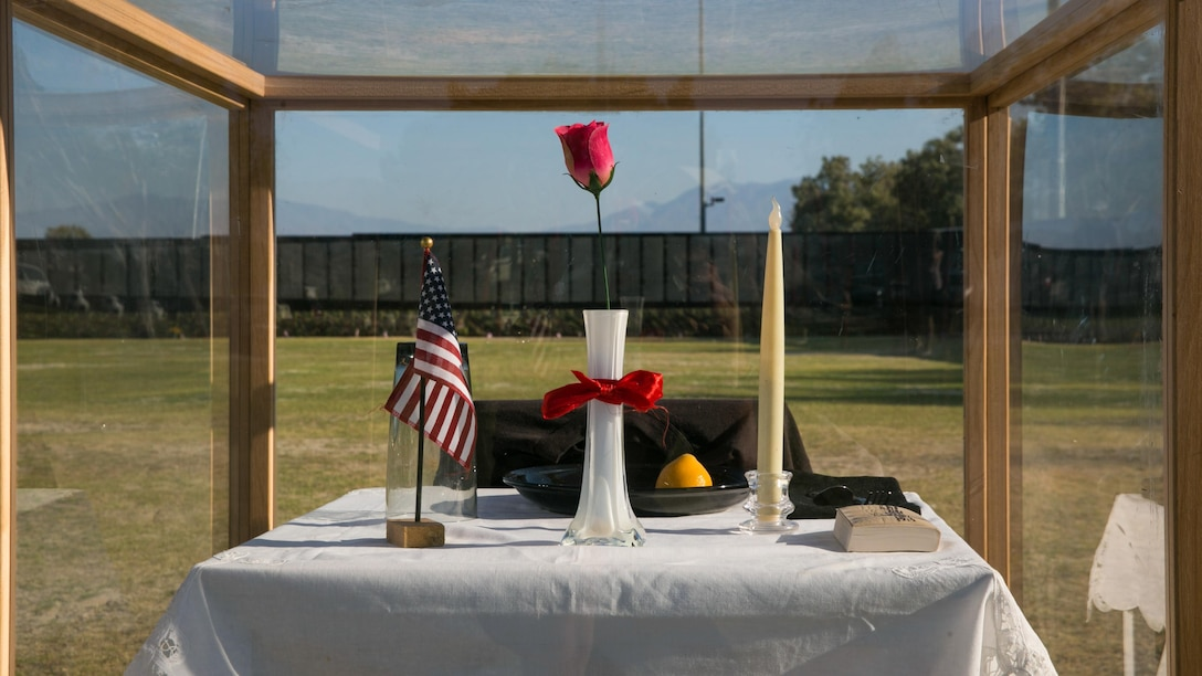 The Prisoner of War/Missing in Action table represents the service members who never had a chance to make it home or could not be found at the opening program of the Moving Vietnam Veterans Memorial Wall at Mission Springs Park in Desert Hot Springs, Calif., June 22, 2017. The Moving Wall, a scale model of the original Vietnam Veterans Memorial Wall, has the names of those men and women who were killed or missing in action etched onto a reflective stone, so visitors can not only see the names, but see themselves, reflecting on the lives of the people who fought and died to keep them safe. (U.S. Marine Corps photo by Cpl. Dave Flores)