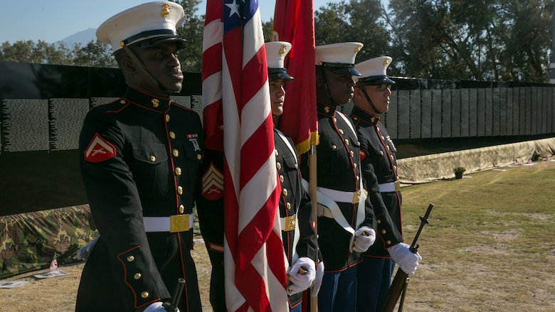 Marines with the Headquarters Battalion Color Guard prepare to present the colors during the opening program of the Moving Vietnam Veteran Memorial Wall at Mission Springs Park in Desert Hot Springs, Calif., June 22, 2017. The Moving Wall, a scale model of the original Vietnam Veterans Memorial Wall, has the names of those men and women who were killed or missing in action etched onto a reflective stone, so visitors can not only see the names, but see themselves, reflecting on the lives of the people who fought and died to keep them safe. (U.S. Marine Corps photo by Cpl. Dave Flores)