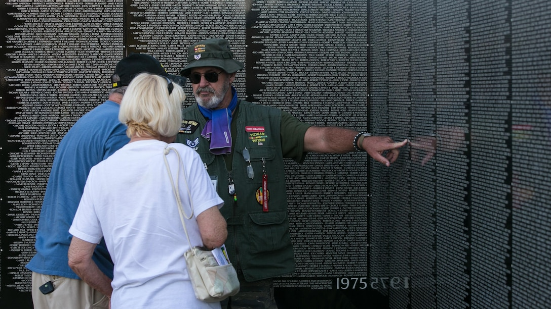 Retired Air Force Staff Sgt. Dennis Blessman speaks to visitors about the Moving Vietnam Veteran Memorial Wall after the opening program at Mission Springs Park in Desert Hot Springs, Calif., June 22, 2017 The Moving Wall, a scale model of the original Vietnam Veterans Memorial Wall, has the names of those men and women who were killed or missing in action etched onto a reflective stone, so visitors can not only see the names, but see themselves, reflecting on the lives of the people who fought and died to keep them safe. (U.S. Marine Corps photo by Cpl. Dave Flores)