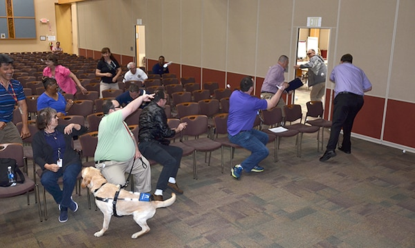 Defense Supply Center Richmond employees throw paper at a mock active shooter, then run away to demonstrate how to disrupt and disorient his thought processes during Active Shooter Awareness and Response Training on DSCR in Virginia, June 23, 2017 in the Frank B. Lotts Conference Center. (Photo by Jackie Roberts)