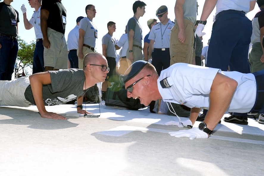 A member of the cadet training cadre at the U.S. Air Force Academy leads a basic cadet through push ups June 29, 2017. Nearly 1,200 basic cadets were scheduled to arrive at the Academy and begin Basic Cadet Training. (U.S. Air Force photo/Jason Gutierrez)