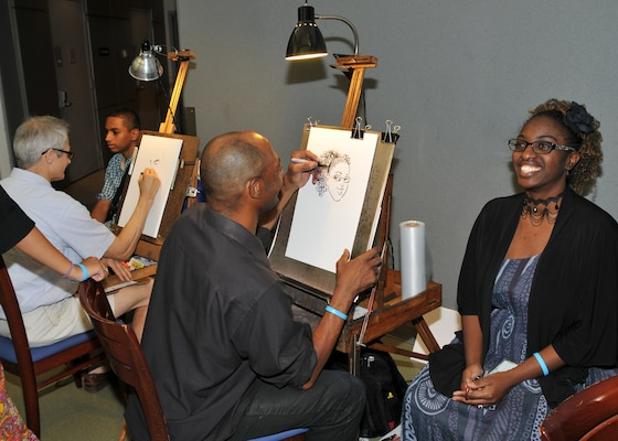Employees and family members sit for free caricatures on Family Day at the McNamara Headquarters Complex.