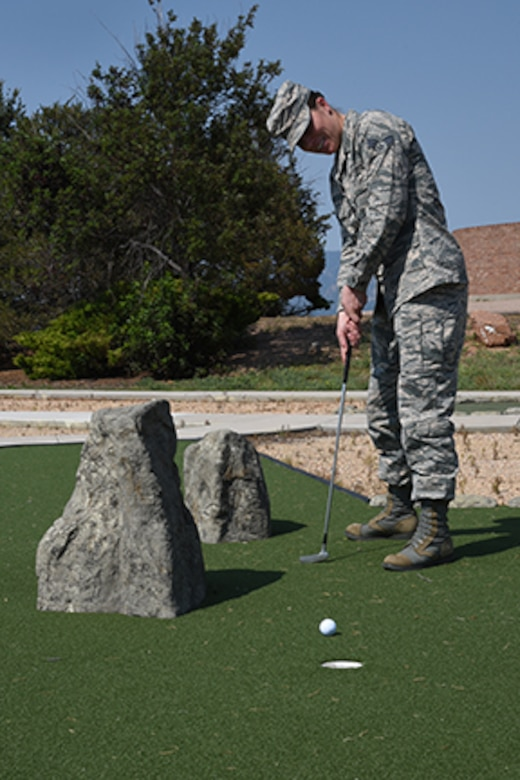 PETERSON AIR FORCE BASE, COLO. – Senior Airman Rose Gudex, 21st Space Wing Public Affairs photojournalist, holes out her putt on the third hole at Peak View Parks Putt-Putt golf course at Peterson Air Force Base, Colo., June 28, 2017. The nine-hole course offers outdoor recreation entertainment for Airmen stationed at Peterson AFB. (U.S. Air Force photo by Robb Lingley)