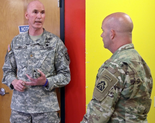 Maj. Edward King (left), medical site officer-in-charge for Larga Vista Community Center, briefs Brig. Gen. John Hashem (right), deputy commanding general-support and director of the Army Reserve Engagement Cell, or AREC, at U.S. Army North (Fifth Army), about the various aspects of medical assistance his unit is providing the community in Laredo, Texas, June 27. At this community, residents received dental exams, health screenings and dietary information.