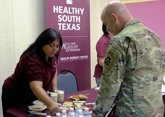Julie Tijerina (left), a program specialist with Webb County's Healthy South Texas, explains the importance of a well-balanced meal to Brig. Gen. John Hashem, deputy commanding general and director of the Army Reserve Engagement Cell at U.S. Army North (Fifth Army), during an Innovative Readiness Training, or IRT, mission June 27 in Laredo, Texas. This was one of the many stations at the Larga Vista Community Center that helped improve medical health for local residents.