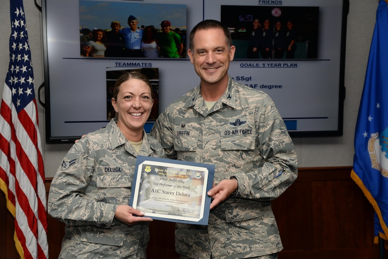 Col. Ethan Griffin, 436th Airlift Wing commander, presents the Top Performer of the Week award to Airman 1st Class Stacey Deluca, 436th Maintenance Squadron Regional Isochronal Inspection Dock consolidated tool krib custodian, during the weekly wing stand up meeting June 7, 2017, at Dover Air Force Base, Del. Deluca was recognized for her outstanding performance above and beyond that expected of an airman first class. (U.S. Air Force photo by Senior Airman Aaron J. Jenne)
