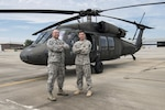 Air Force Senior Master Sgt. Edward Snyder, with the South Carolina Air National Guard's 169th Fighter Wing, stands with his son, 2nd Lt. Michael Snyder, assigned to the Carolina Army National Guard's Alpha Company, 1st Battalion, 111th Aviation Regiment, near a UH-60 Black Hawk helicopter at McEntire Joint National Guard Base in Eastover, S.C., June 13, 2017. The senior Snyder's example of service to others inspired his son to join the National Guard and become a Black Hawk pilot. South Carolina Army National Guard photo by Spc. Chelsea Baker
