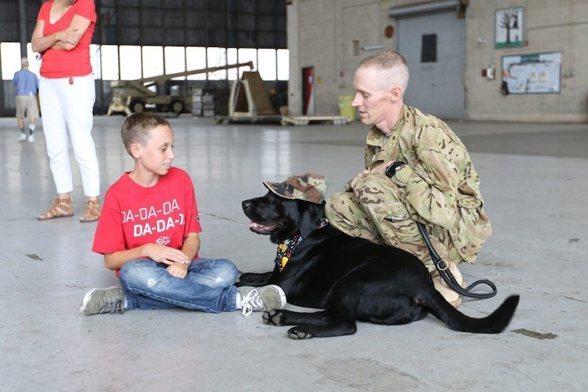 Army Chief Warrant Officer 4 Chris Hellums and his son, Gabriel, sit with Kyle, an ambassador dog for Southeastern Guide Dogs, at Hunter Army Airfield, Ga., June 26, 2017. Kyle became the ambassador dog after being diagnosed with an injury. Army photo by Staff Sgt. Kellen Stuart