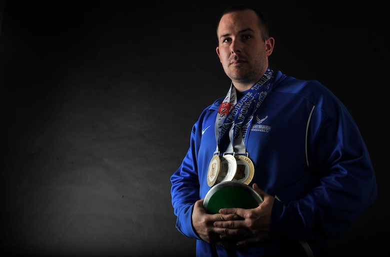 Retired U.S. Air Force Staff Sgt. Clifton Flint, formerly 48th Security Forces Squadron base defense operations center controller, poses for a photo June 30, 2017, on RAF Mildenhall, England, with his discus and the bronze, silver and gold medals he earned at the Wounded Warrior Air Force Games held at Nellis Air Force Base, Nevada, earlier this year. Flint suffers from post-traumatic stress disorder, brought on after sustaining a traumatic brain injury while deployed to Iraq in 2005. (U.S. Air Force photo by Staff Sgt. Micaiah Anthony)