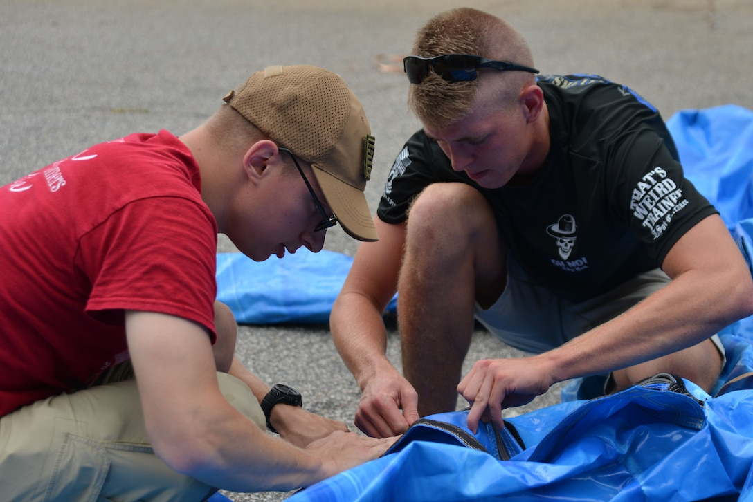 U.S. Air Force Airman 1st Class Zachary Voreh, 20th Force Support Squadron (FSS) services journeyman, left, and Airman 1st Class Jason Ridley, 20th FSS services apprentice, put together a bouncy slide near the Woodland Pool at Shaw Air Force Base, S.C., June 30, 2017. The two volunteered to help prepare the area for the Freedom Bash, an annual Team Shaw Independence Day celebration. (U.S. Air Force photo by Airman 1st Class Destinee Sweeney)
