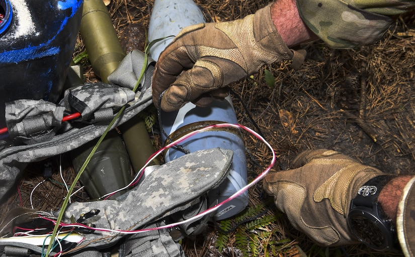 Senior Airman Dylan Babb, 628th Civil Engineer Squadron explosive ordnance technician, investigates a weapons cache during training operation Mogul Wrath, June 27, 2017. EOD here trained over the course of a week to ensure they are retaining knowledge and can efficiently use their skillsets in real world situations.