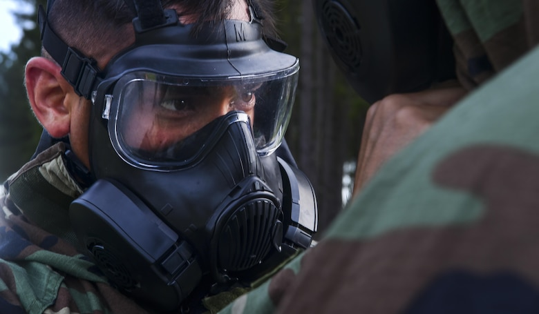 Staff Sgt. Eric Jones, 628th Civil Engineer Squadron explosive ordnance disposal technician, helps his wingman with his gas mask during training, June 28, 2017. During exercise Mogul Wrath, teams completed training events which used various practical skills, EOD specialized equipment and scenario-based full spectrum emergency responses.