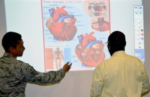Senior Airman Travis Napaepae (left), Medical Education and Training Campus Information Management Division call center manager, and Eustace Lewis, METC  instructional system specialist, talk about the interactive SMART screen display of a heart.