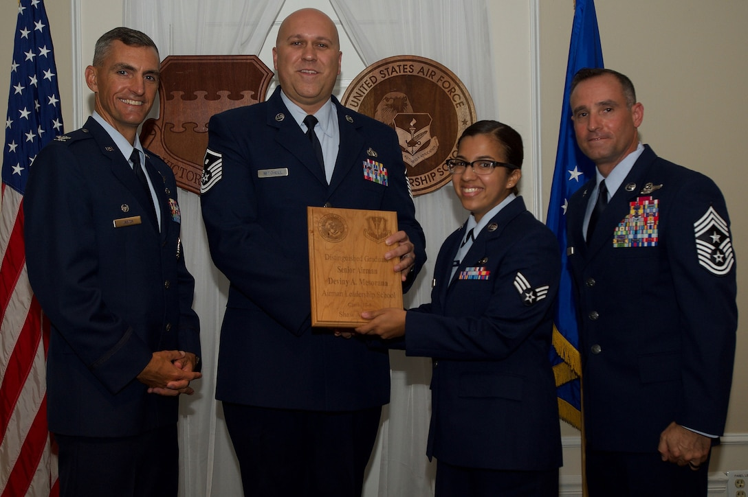 U.S. Air Force Senior Airman Deviny Mesorana, 31st Intelligence Squadron, receives a Distinguished Gradate Award during the Senior Master Sgt. David B. Reid Airman Leadership School Class 17-5 graduation ceremony at Shaw Air Force Base, S.C., June 30, 2017. Distinguished graduate awards are given to the top 10 percent of the class for total point accumulation. (U.S. Air Force photo by Senior Airman Michael Cossaboom)