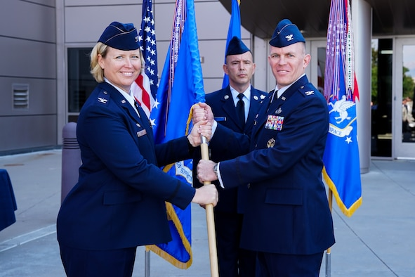 Col. DeAnna Burt, 50th Space Wing commander, passes the 50th Mission Support Group guidon to Col. Brian Kehl during the group's change of command ceremony at Schriever Air Force Base, Colorado, Tuesday, June 27, 2017. Kehl assumed command of the group from Col. Jason Janaros. (U.S. Air Force photo/Christopher DeWitt)