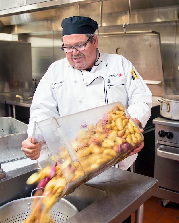 Maynard Oestreich, executive chef for Aramark prepares meals prior to the Airmen Leadership School graduation at Travis Air Force Base, Calif., June 28, 2017. Oestreich a former U.S. Navy veteran and an award-winning chef from Napa Valley, Calif., took the head chef position so he could mentor young Airmen. (U.S. Air Force photo by Louis Briscese)