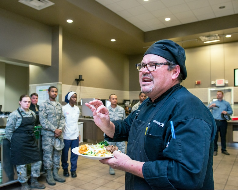 Maynard Oestreich, executive chef for Aramark explains his dish during the BIBIM Box tasting featuring Korean food at Sierra Inn Dining Facility, Travis Air Force Base, Calif., June 29, 2017. Oestreich a former U.S. Navy veteran and an award-winning chef from Napa Valley, Calif., took the head chef position so he could mentor young Airmen. (U.S. Air Force photo by Louis Briscese)
