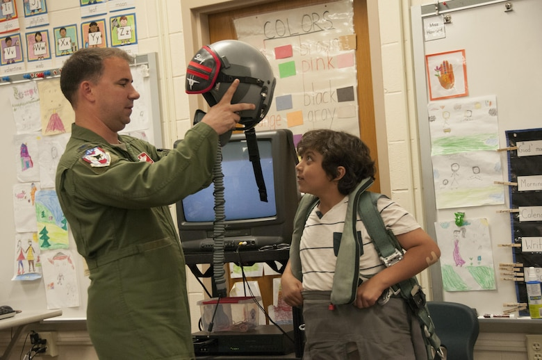 Col. Tom Bladen, 104th Fighter Wing operations group commander, visits refugee students at Highland Elementary School in Westfield, Massachusetts, June 26, 2017. The visit served as a means to help the children understand why they hear the loud screeching F15 jets flying overhead when playing outside and to help them understand the 104th Fighter Wing flies to protect. Bladen helps the honoree pilot of the day dawn a 104th Fighter Wing flight suit. (U.S. Air National Guard photo by Senior Master Sgt. Julie Avey)