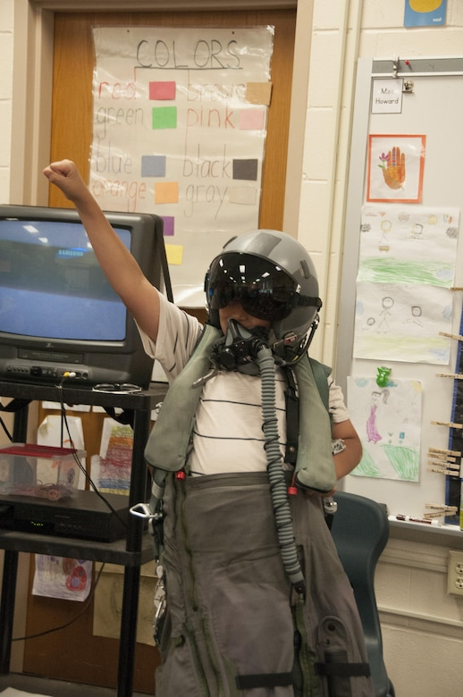 A 10-year-old Hadi Al Nassar, cheers as he wears a 104th Fighter Wing flight suit and aviator helmet as the honoree pilot of the day, June 26, 2017. Tom Bladen, 104th Fighter Wing operations group commander, visits refugee students at Highland Elementary School in Westfield, Massachusetts. The visit served as a means to help the children understand why they hear the loud screeching F15 jets flying overhead when playing outside and to help them understand the 104th Fighter Wing flies to protect. (U.S. Air National Guard photo by Senior Master Sgt. Julie Avey)