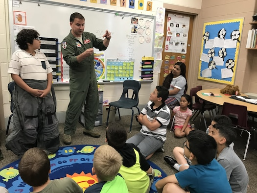 Col. Tom Bladen, 104th Fighter Wing operations group commander, visits refugee students at Highland Elementary School in Westfield, Massachusetts, June 26, 2017. The visit served as a means to help the children understand why they hear the loud screeching F15 jets flying overhead when playing outside and to help them understand the 104th Fighter Wing flies to protect. Bladen explains how the flight suit prevents the pilots from passing out while flying as he speaks to the students after helping the honoree pilot of the day dawn a 104th Fighter Wing flight suit. (U.S. Air National Guard photo by Senior Master Sgt. Julie Avey)
