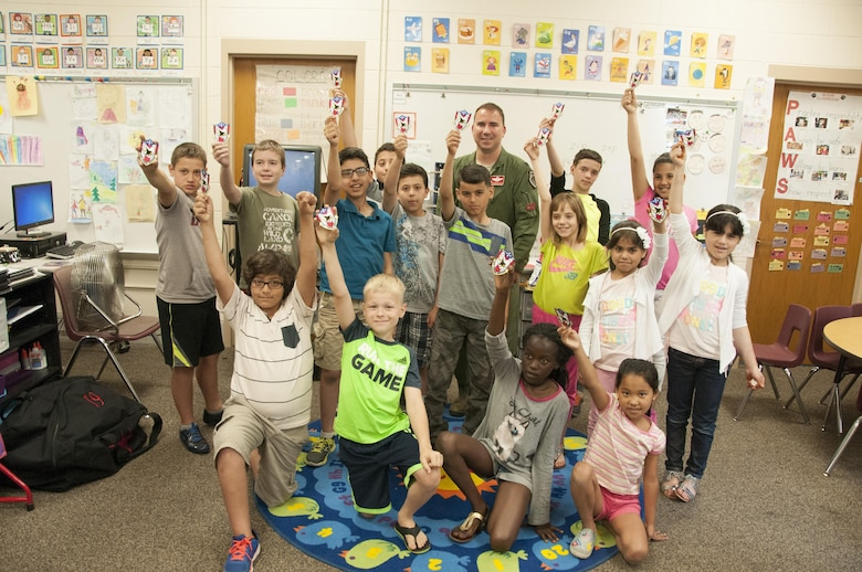 Col. Tom Bladen, 104th Fighter Wing operations group commander, visits refugee students at Highland Elementary School in Westfield, Massachusetts, June 26, 2017. The students received a 104th Fighter Wing patch and raised the patch up high while taking a photo with Col. Bladen after hearing about the 104th Fighter Wing mission to protect and serve. The visit served as a means to help the children understand why they hear the loud screeching F15 jets flying overhead when playing outside and to help them understand the 104th Fighter Wing flies to protect. Bladen speaks to the students about the F-15 Eagle and explains to the refugee students on how the pilots practice a lot just as soccer players practice. (U.S. Air National Guard photo by Senior Master Sgt. Julie Avey)